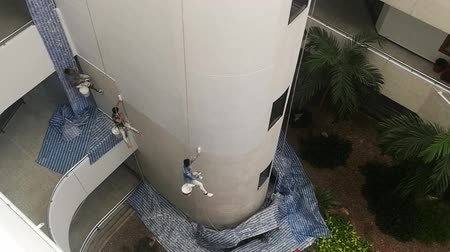 work at height : Bangkok, Thailand - December,3 2018 :  Painters are painting on high buildings with the big rope. Stock Footage