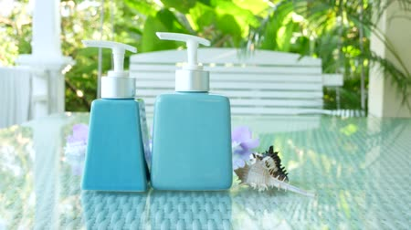 sanitize : Blue bottle Hand & Body Cream on table with nature background