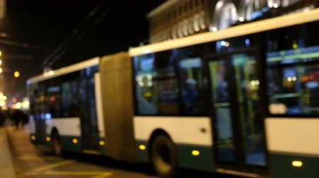 население : Blurred bus on the street at night.