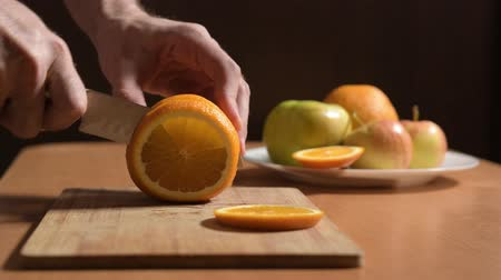 ингредиент : Mans hands cutting fresh orange on kitchen Стоковые видеозаписи