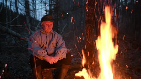 Old man warm near campfire
