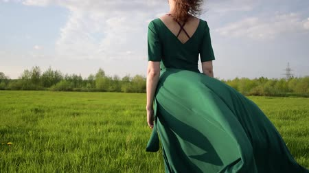 raised : Young beautiful woman in a beautiful dress is standing in a field at sunset