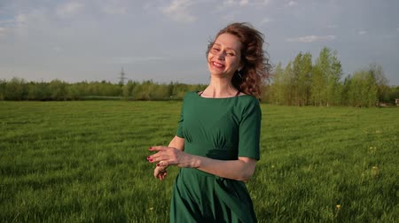 Young happy beautiful woman in a dress runs along the green field
