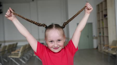 косички : Little girl playing with pigtails. Beautiful girl plays with her hair