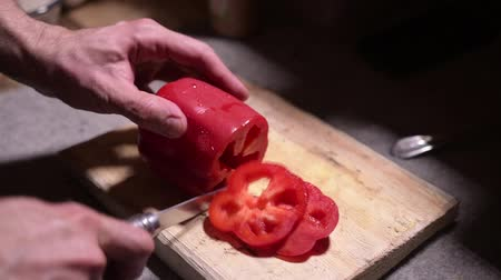 Knife cuts the red pepper. A large red sweet pepper is cut on a cutting board. Bulgarian pepper.