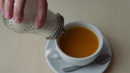 adoçante : Woman hand adds a lot of sugar to tea from sugar bowl, unhealthy food concept