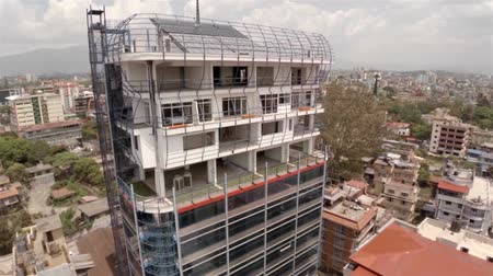 panel buildings : Office building under construction in Kathmandu drone footage. Solar panels and antenna on the roof.
