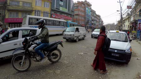 boudha : KATHMANDU, NEPAL - CIRCA FEBRUARY 2018: Traffic on Boudha Road, next to the entrance to Boudhanath stupa.
