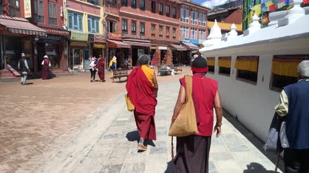 bodhnath : KATHMANDU, NEPAL - CIRCA SEPTEMBER 2018: A buddhist monk walks around Boudhanath stupa and spins prayer wheels. With 3D audio. Stock Footage