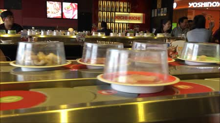 hentes : Saigon, Vietnam - December 09, 2015: Trays of food moving in line in a Japanese reataurant