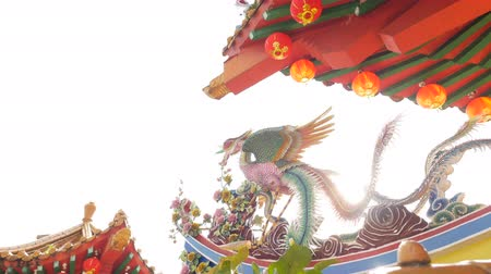 anka kuşu : Camera movement reveals a backlit phoenix. Lens flare is created by the sun. A traditional chinese buddhist temple architecture is in the background. Red lantern is hanging off the temple structure Stok Video