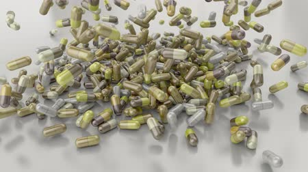 depressant : Pills drugs capsules falling on white table counter top slow motion closeup 4K