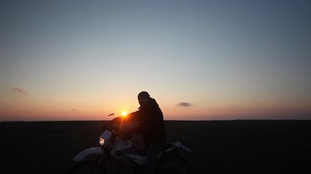 autobike : Silhouette of the motorcyclist on a background of sunrise and the windsock