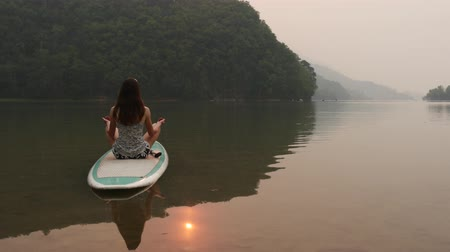 remo : Woman meditates on paddleboard