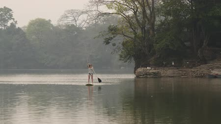 bordo : Woman floats on paddleboard on the river in the rainforest
