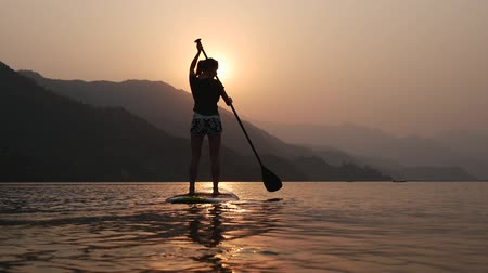 bordo : Girl floats away into the distance on paddleboard