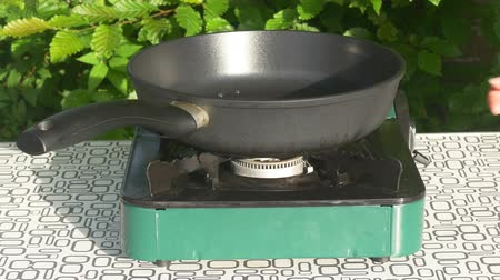 fogão : A person turns up the heat on a camping gas stove with a frying pan on.