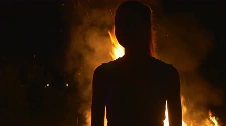 yanmak : Silhouette of a young woman on in front of fire
