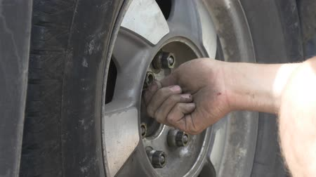 dirty : Man replaces tire on a roadside