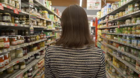 corredor : Woman walking along shelves with products
