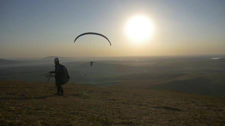One paraglider flies in front of the mountain, the second prepares to take off Стоковые видеозаписи