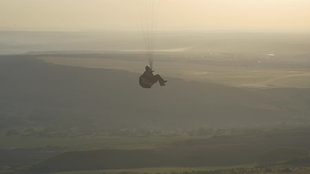 Paraglider in the harness climbs