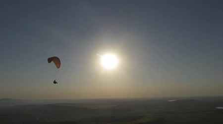 скольжение : Two paragliders fly against the sun Стоковые видеозаписи