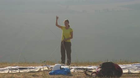 Woman pilot paraglider prepares to take off