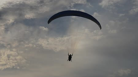 padák : Paragliding tandem against a blue evening sky and rainbow