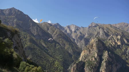 Paragliders gaining altitude in the mountains