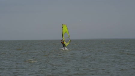 Girl on the windsurf floats away into the distance
