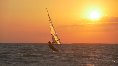 Shining water droplets on a windsurf sail in the sunset Стоковые видеозаписи