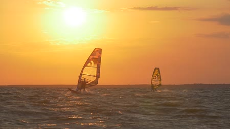 Two windsurfers on the sea at sunset