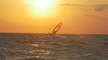Windsurfer jumping against the setting sun