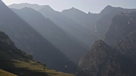 dolomitok : Strips of light rays in the mountains and a lone paraglider Stock mozgókép