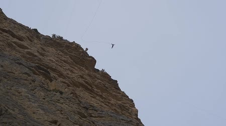 riskantní : Jumping with a rope from a cliff