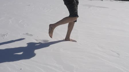 boldness : Man walks on fresh untouched snow barefoot