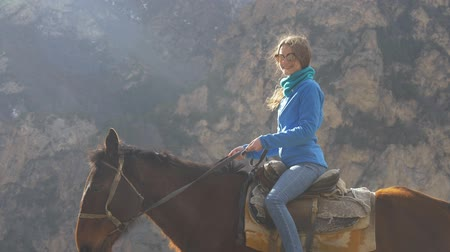 dizgin : Portrait of a girl riding a horse on a background of mountains Stok Video