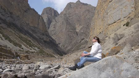 dinlenmek : Woman in a white sweater among the rocks