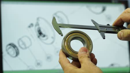 ložisko : Mechanic selects a bearing according a drawing