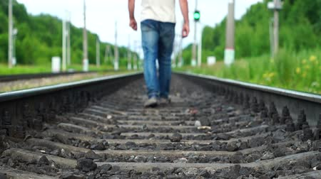 тапки : Man walking away along railway track Стоковые видеозаписи
