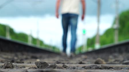 Lonely man walking away along railway track into blur Wideo