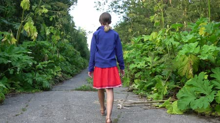 Girl goes along abandoned road overgrown by hogweed Wideo