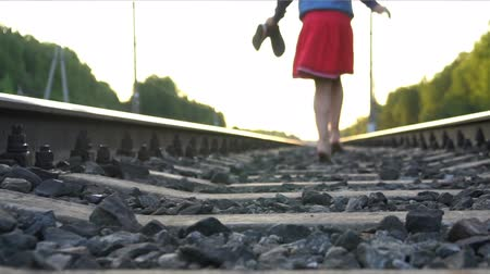 Teenager girl running barefoot away on railway