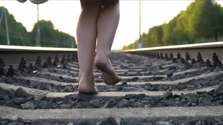 jump away : Young barefoot girl running away on railway Stock Footage