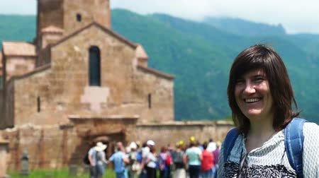 Summer shot of a female caucasian tourist in front of ancient armenian church Wideo
