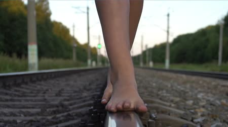 Girl walking barefoot along railroad rail