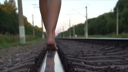 sleepers : Young girl walking barefoot along railroad rail