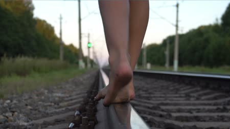 jump away : Teen girl walking barefoot along railroad rail Stock Footage