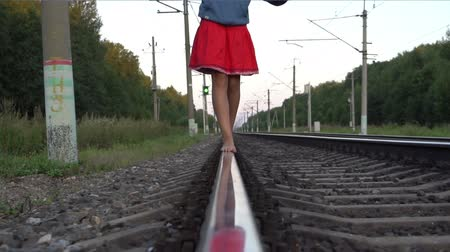 Teenager girl walking barefoot along railroad rail Wideo